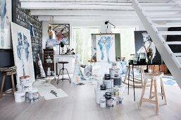 Pots of paint, desk and artworks in painter's studio