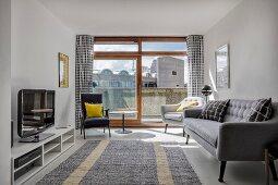 Retro sofa and armchairs in front of open balcony door in living room