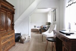 Antique cupboard, desk below window in open-plan study area and view into lounge area through open doorway