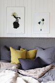 Scatter cushions arranged against grey upholstered headboard below framed pictures on white wood-clad wall