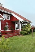 Falu-red wooden house with veranda and garden