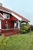 Rotes Holzhaus mit Veranda und Garten