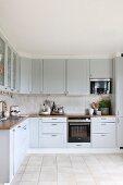 Einbauküche mit hellgrauen Schrankfronten und beigefarbener Fliesenboden