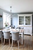 Pale grey upholstered chairs around wooden table below chandelier in traditional, Scandinavian-style dining room