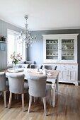 Hellgraue Polsterstühle um Holztisch darüber Kronleuchter in traditionellem Esszimmer im skandinavischen Stil