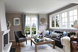 Fireplace, upholstered furnishings and white lattice windows in cosy living room