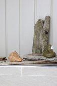 Badeente auf Treibholzstück und Muschelgehäuse auf Badablage