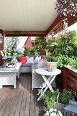Comfortable corner sofa, coffee table, herbs, climbing roses and hanging baskets on veranda