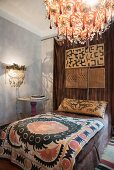 Lamps with glass pendants, ethnic bedspread and ornate pillow in bedroom
