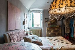Bed with patterned headboard and lit, artistic lampshade in bedroom