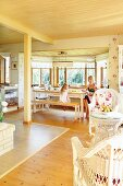 Open-plan interior with pale wooden ceiling, wicker furniture and mother and daughter in dining area in window bay