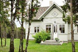 Blick vom Garten auf Landhaus mit hellgrau gestrichener Holzverschalung und Anbau mit Giebelfront
