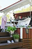 Summery veranda painted reddish brown with seating area and white wicker chairs next to wooden steps