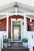 Open front door on wooden veranda decorated with potted plants