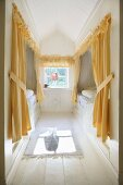 Bright, wood-clad attic bedroom with yellow curtains and pelmets on cubby beds