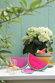 Hand-made, watermelon-slice invitation cards made from folded paper on garden table