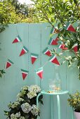 Hand-made bunting on green wooden fence in garden