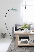 Grey couch, arc lamp and vase of flowers on solid wooden coffee table in elegant living room