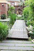 Wooden bridge spanning garden pond and leading to house with terrace