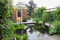 Bridge spanning garden pond and leading to terrace and house