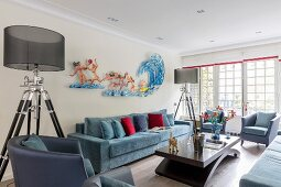 Two standard lamps with transparent lampshades flanking blue sofa and artwork on wall of elegant lounge