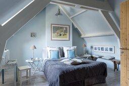 Schlafzimmer in Blautönen unter dem Dach mit Holzbalken