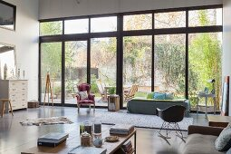 Glass wall in open-plan eclectic interior with view of garden
