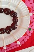 Cherries stuck on decorated wooden skewers on white plate