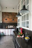 Black kitchen counters, brick wall, pendant lamps and charcoal concrete floor in loft apartment