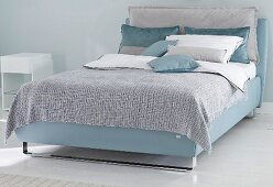 A boxspring bed in blue tones in a bedroom