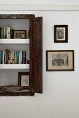 Bookshelves in niche with rustic shutter doors