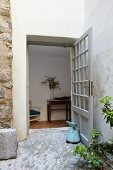 Terrace with stone floor and lattice door leading into hallway with console table