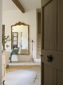 Mirror and tall candlestick seen through open door