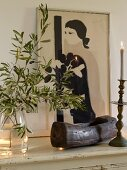 Olive branch in glass jar, wooden bowl, candlestick and picture of woman on white surface
