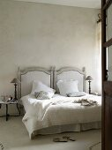 French bed with grey wooden headboard and lamp on side table in bedroom