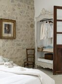 Open-fronted wardrobe and stone wall in rustic bedroom