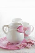 White milk jug with hand-made pink felt drip catcher and coaster