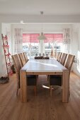 Solid wooden table and wicker chairs in festively decorated dining room
