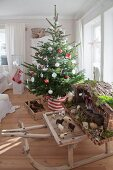 Decorated Christmas tree and traditional nativity set on vintage wooden sledge