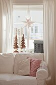 Comfortable loose-covered sofa in front of festively decorated lattice window