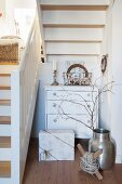 Festively decorated chest of drawers and wrapped gift below white wooden staircase