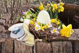 Egg-shaped candles and flowers in Easter nest made from twigs