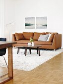Nesting coffee tables and a brown leather sofa on a white flokati rug with landscape pictures in the background