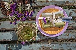 Gedeck mit Stoffserviette, Besteck und lila Krokussen auf Holzuntergrund