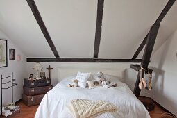 Teddy bear and scatter cushions on double bed next to stacked vintage suitcases below sloping ceiling in renovated farmhouse