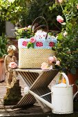 Raffia shopping bag decorated with knitted trim and knitted roses on garden terrace with vintage accessories