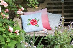 Romantic, knitted cushion cover with rose motif on rustic garden bench