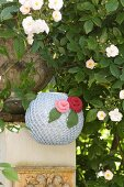 Romantic, knitted lantern decorated with knitted flowers hung below white climbing rose