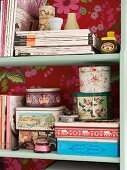 Magazines and vintage tins on shelving with back wall papered with red floral wallpaper