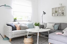 White coffee table and sofas with different covers below window with closed blind in corner of living room